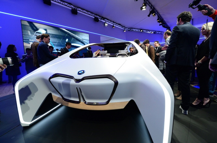 Crowds gather to see a BMW prototype vehicle at the BMW Group news conference. The BMW Group, Intel, and Mobileye on Wednesday, Jan. 4, 2017, announced that a fleet of about 40 autonomous test vehicles will be tested on the roads by the second half of 2017. The event was a lead-in to the 2017 International Consumer Electronics Show. The event runs from Jan. 5 to Jan. 8, 2017, in Las Vegas. (CREDIT: Walden Kirsch/Intel Corporation)